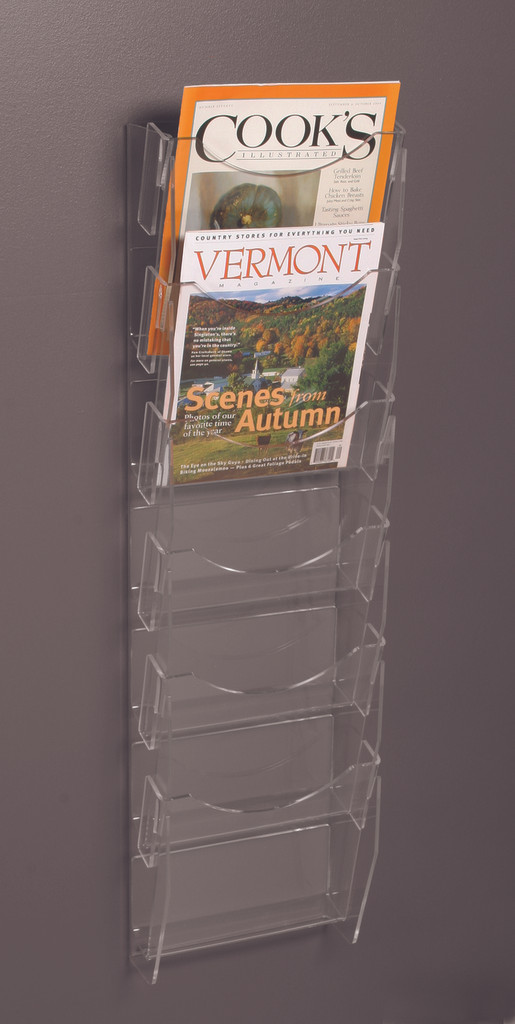 Clear acrylic six pocket wall mounted ladder for displaying magazines, brochures, and other printed materials.