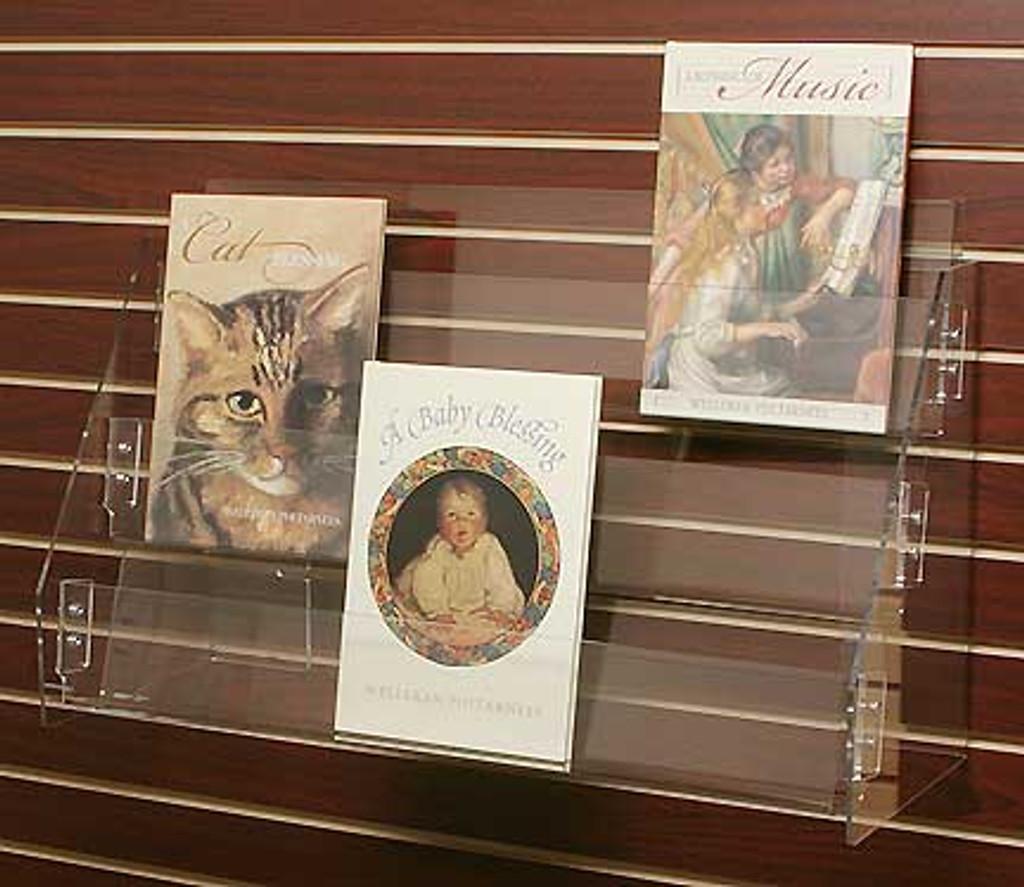 Heavy clear acrylic slatwall mounted triple shelf for books, magazines, and calendars.
