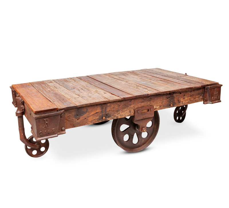 Recycled Timber Cart Coffee Table - A low coffee table for the contemporary rustic space featuring a large cart wheel and 2 swivel wheels. Inspired by the distinctive vintage look of the pre-industrialised era, each piece is hand crafted with reclaimed timber which retains it's organic characteristics and is set off by rustic metal detailing. Add industrial edge to your living space. Three quarter view .