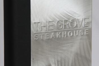 Embossed logo on an aluminum menu cover.