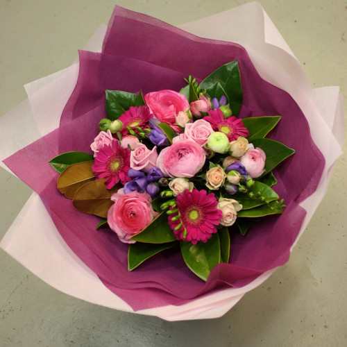 Hand tied bouquet of bright and pale pink flowers with a splash of lavender, includes freesias, roses and gerberas.
