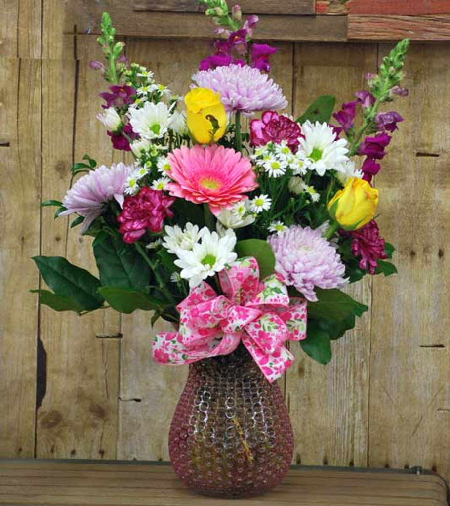 vase arranged perfectly with bright cheerful flowers personally arranged in it just for you.