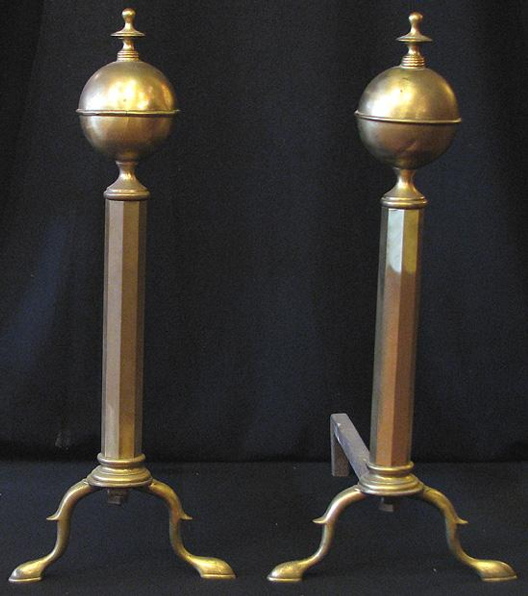 Pair of antique brass andirons with ball and finial tops and pad feet.