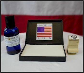 Two ounce ink bottle next to the open pad waiting for the smile wood stamp.
