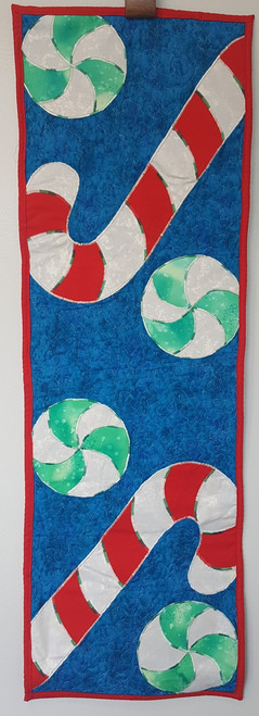 This can be a table runner or a festive wall hanging.  It is made from cotton fabrics and measures 13 by 40 (approximately)  A fun thing for the holidays and one of a kind!