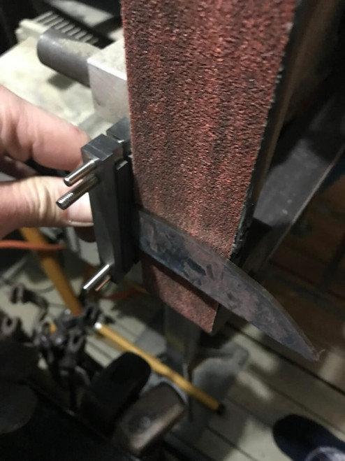 Showing a blade clamped in the file guide and the bevel being ground on the platen. This smaller version fits easier on either side of the platen, here on a Noob grinder.