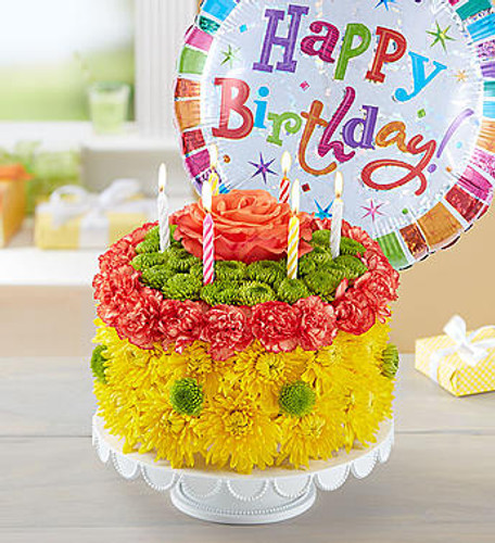 Birthday Wishes Flower Cake™ Yellow EXCLUSIVE Be the reason their birthday is brighter! Our cheerful cake creation is crafted with a vibrant mix of blooms for a fun and lively birthday celebration. Served up on a pedestal stand and topped with candles, it's a truly original, festive way to celebrate somebody special. Take happy to new heights by adding a balloon to their gift.