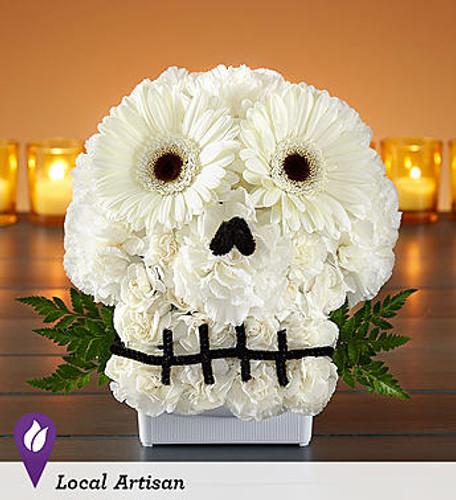 "Spooky Skull Flower Arrangement™ DESIGN COUNCIL EXCLUSIVE Make no bones about it… our truly original skull creation will get everyone into the Halloween spirit. Crafted from all-white blooms, this to-die-for design was made by Sarah Jean from the product development team at 1-800-Flowers.com. ""When I came up with it, I was thinking about my daughter. She basically grew up in a flower shop, and I knew it would bring a smile to her face to see something so different and playful."" Lighten up the fright by adding a bright, colorful floral tiara for the skull."