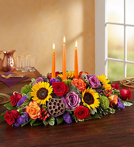 Garden of Grandeur™ for Fall Centerpiece Autumn gatherings call for a grand centerpiece. We've designed our luxurious arrangement with a mix of brightly-colored blooms and unique, textural accents, creating a truly unique table display. A trio of orange candles provides the perfect finishing touch, adding warmth and coziness to spirited celebrations with family an