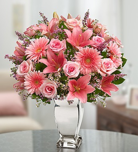 EXCLUSIVE One look at this truly original arrangement of pink roses, lilies, Gerbera daisies and more will leave her smiling brighter than the vase it arrives in! We think it's a brilliant gift idea for birthdays, anniversaries or any day you want to put that special someone in the spotlight.