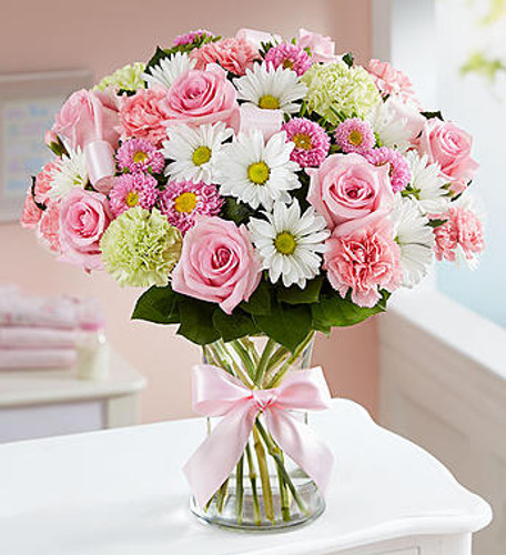 Sweet Baby Girl™ Arrangement A precious baby girl has arrived and you couldn't be happier! Surprise the proud new parents with our perfectly-girly pink bouquet. Designed inside a glass vase finished with pink ribbon  accents, it's a sweet way to welcome their little bundle of joy into the world.