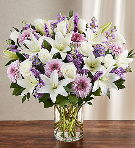 Sincerest Sorrow™ Lavender & White Let a deeply heartfelt sentiment be delivered in true form. Our lush, bountiful bouquet of lavender and white blooms features an elegant mix of roses, lilies and cremones, hand-designed inside a classic clear glass vase. When sent to a service or to the home of family or friends, it makes a genuinely heartwarming gesture.