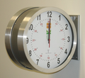 """DuraTime 12"""" Double Sided Brushed Aluminum Analog Clock, Battery Operated. Available in 12"""" and 15"""" diameter. Contact us for advice and prices."""