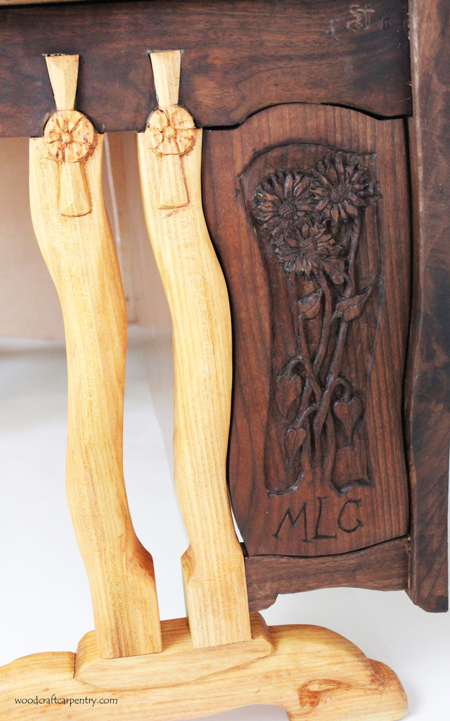 Closeup of Hand Carved Panel with Flowers and Initials of Owner of Desk.  Legs are handcarved Locust wood.