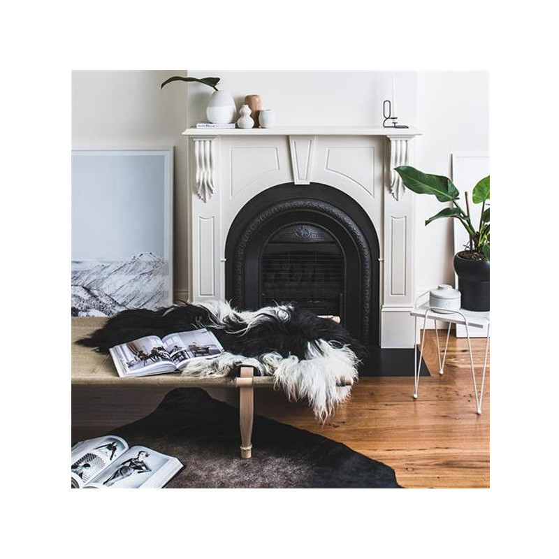 Icelandic Sheepskin Throw Rug in Black with White Spot. Add warmth, texture and luxury to your space with this naturally silky soft long haired Icelandic Merino sheepskin throw rug in black with white spot. Styled view.