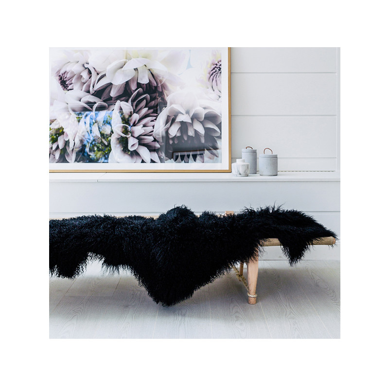Mongolian Sheepskin Throw Black. Add warmth, texture and luxury to your space with this naturally silky soft sheepskin throw rug in black.  Style shot.