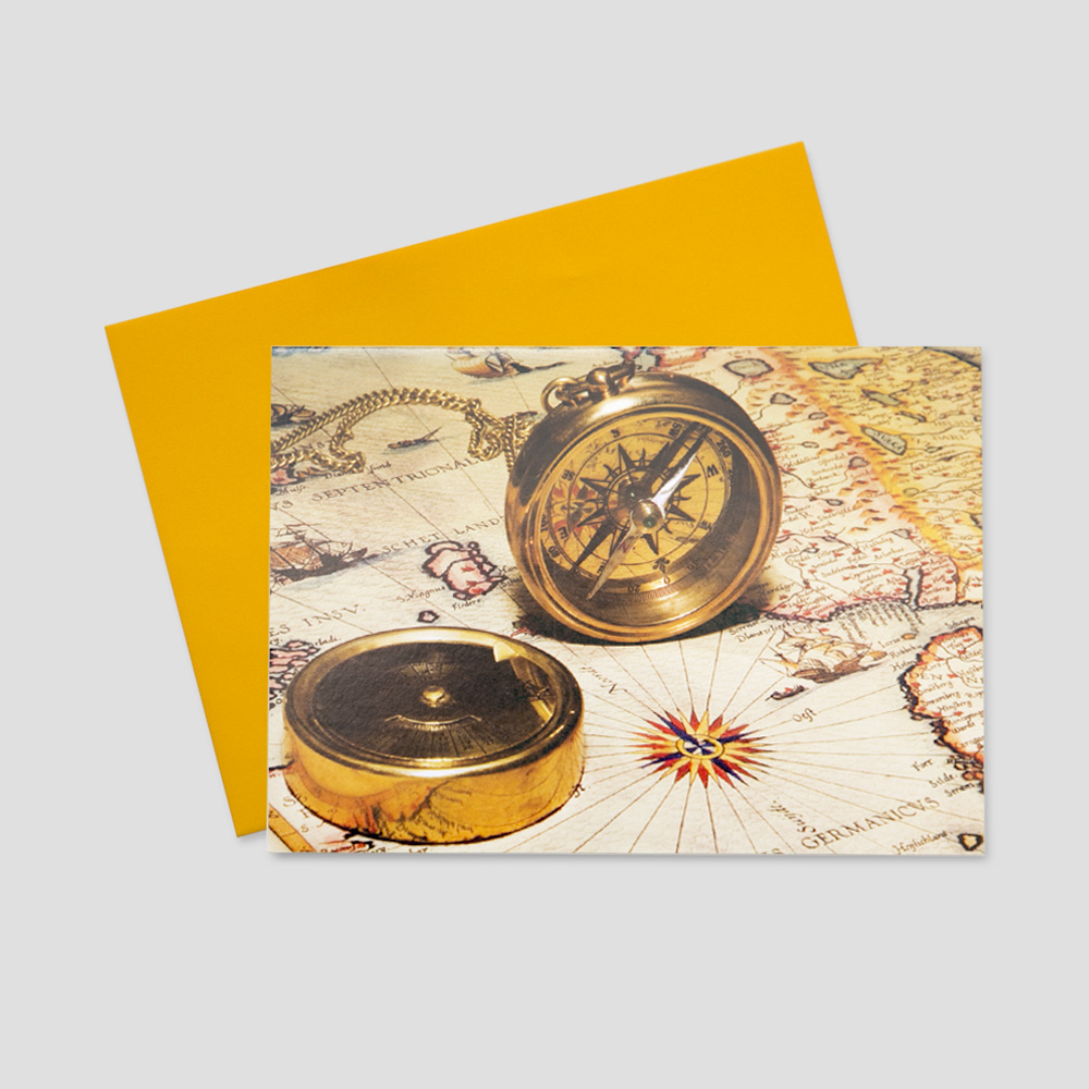 Customer keep in touch greeting card featuring a golden compass sitting on an old colorful map