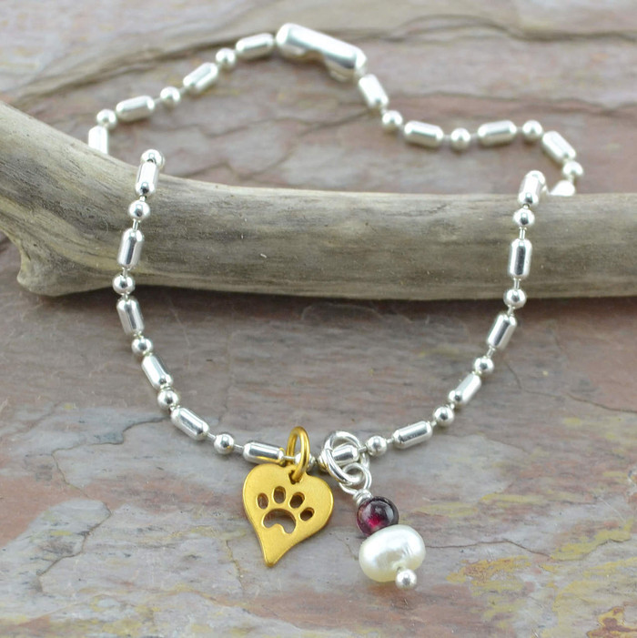 Handmade charm bracelets made with garnet and pearl gemstone and paw print: view 1