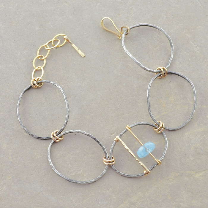 Unique chain link bracelet made with sterling silver in oval shapes and an aquamarine gemstone
