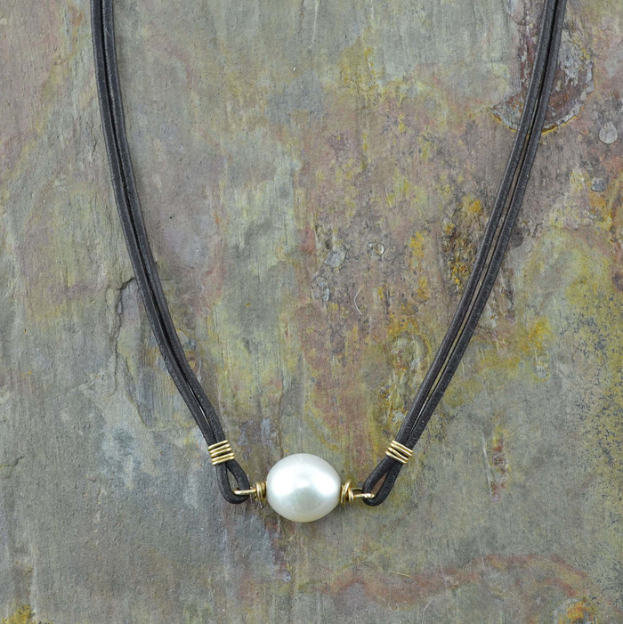 Handmade pearl necklace suspended between two leather cords: view 1