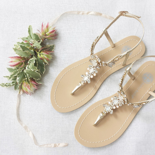Thong sandal Vintage-inspired rows of crystal jewels and white onyx-like stones Jewels set on gold metal plate Light blue sole for your 'something blue' You can rewear them as dressy sandals after your wedding day Soft gold color Adjustable buckle closure Genuine leather upper Leather sole Perfect for casual or bohemian brides Perfect for all occassion; beach weddings, reception, or the dance floor Re-wear them after your special day - perfect for summer nights out Sizing runs true to size