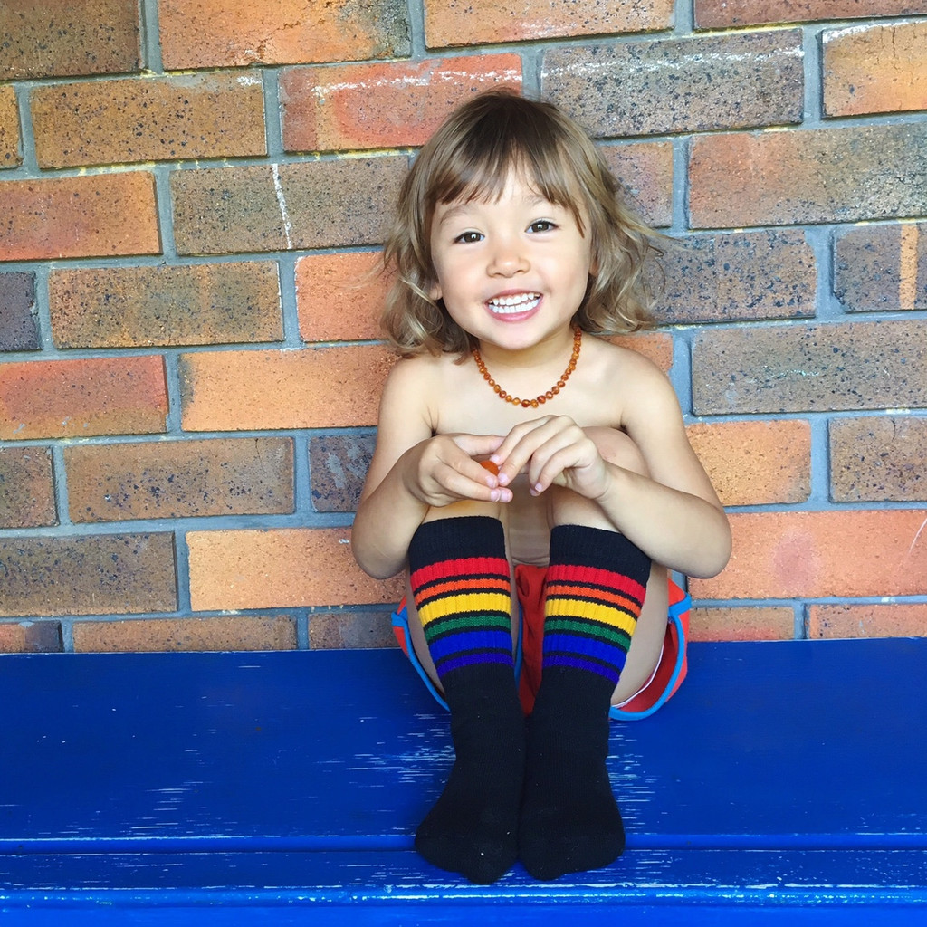 all smiles because I have my cool toddler rainbow brave socks on.