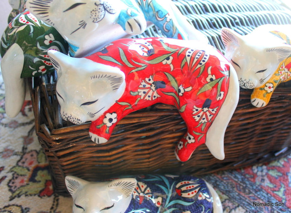 Hand painted ceramic cat with it's leg and paw hanging over the ledge. 5 colours.  Made in Turkey. Large.