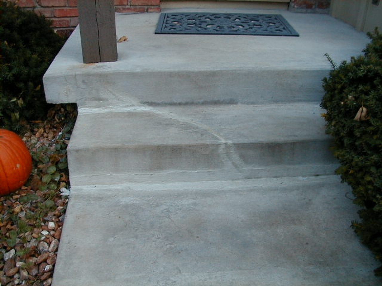 Typical crack repaired with a stiff concrete repair material.  This type of  crack repair will fail at first movement of the concrete step.