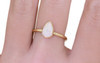 .65 carat pear white opal in 14k yellow gold half round band on a hand