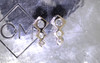 Front view on metal background with Chinchar/Maloney logo of pair of earrings.  Earrings are in dangle position.  Three square-diamond shapes in decreasing size make up the ear climber with brilliant, round gray diamonds are set into the earring also in decreasing size order.