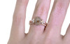 1.42 carat hexagonal, rose-cut gray and peach prong set diamond ring set in 14k rose gold with six 2mm brilliant white diamond clusters on either side of main setting flat band. Wedding Band with 16 brilliant white diamonds in 14k rose gold 1/2 round band on a hand