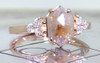 1.42 carat hexagonal, rose-cut gray and peach prong set diamond ring set in 14k rose gold with six 2mm brilliant white diamond clusters on either side of main setting flat band. 3/4 view on metal background with Chinchar/Maloney logo