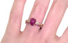 14k yellow gold wedding band with 16 brilliant rubies set half way around band modeled on hand with ruby ring