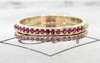 14k yellow gold wedding band with 16 brilliant rubies set half way around band on metal background with Chinchar/Maloney logo