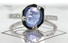 KIKAI 1.37 carat free form rose cut blue sapphire with six 1.2mm brilliant white diamonds set in band set in 14k white gold flat band. Front view on metal background with Chinchar/Maloney logo Part of our New Classic Collection