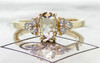 .79 carat oval, rose-cut prong set champagne diamond ring with six 2mm brilliant gray diamond clusters on either side of main setting set in 14k yellow gold flat band. Front view on metal background with Chinchar/Maloney logo