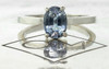 1.59 carat oval rose cut blue sapphire set in 14k white gold flat band. Front view on metal background with Chinchar/Maloney logo