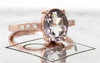 1.99 carat oval faceted cut light pink morganite with six 1.2mm brilliant white diamonds in band set in 14k rose gold flat band. 3/4 view on metal background with Chinchar/Maloney logo