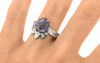 """one-of-a-kind, partially hand-cut and polished, 1.96 carat tanzanite ring. prongs in our original design have been inlaid into grooves carved into the gem for a secure and smooth setting. Six 1.2mm brilliant gray diamonds have been bead-set into the band on each side of the tanzanite. 14k recycled white 2mm wide flat gold band. With Pear Shadow Band features 7 brilliant white diamonds set in """"star"""" settings. 4k recycled white gold and 14k recycled rose gold this ring can also be made in 14k recycled yellow gold on a hand."""
