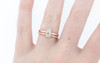 14k rose gold wedding band with 16 brilliant white pave diamonds half way around band modeled on hand with icy diamond ring
