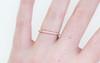 14k rose gold wedding band with 16 brilliant white pave diamonds half way around band modeled on hand