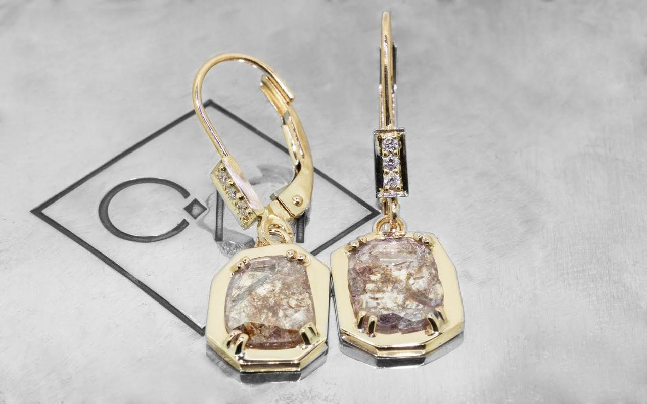 ASKJA 14k yellow gold dangle earrings with 1.08 carat free form cognac and translucent diamonds prong set in geometric 14k yellow gold setting. Three brilliant white diamonds set into front of lever back. Shown on metal background with Chinchar/Maloney logo