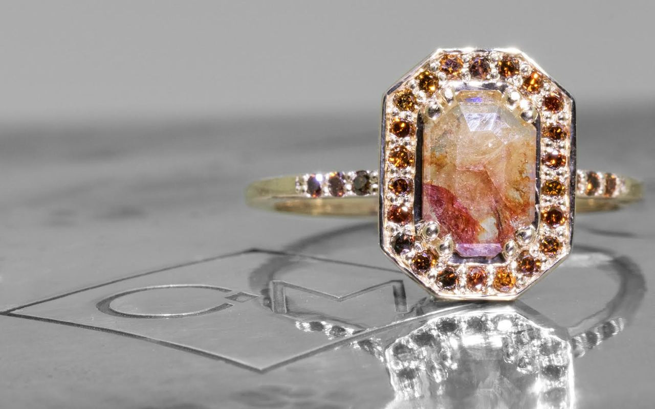 KATLA New Classic .60 carat fancy cut cognac champagne diamond prong set in octangualr  14k yellow gold setting with brilliant, cognac diamonds surround the center diamond in a halo as well as each corner of the setting and each shoulder of the ring. Shown on metal background with Chinchar/Maloney logo