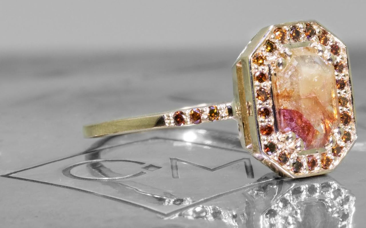 KATLA New Classic .60 carat fancy cut cognac champagne diamond prong set in octangualr  14k yellow gold setting with brilliant, cognac diamonds surround the center diamond in a halo as well as each corner of the setting and each shoulder of the ring. Shown on metal background with Chinchar/Maloney logo. 3/4 view