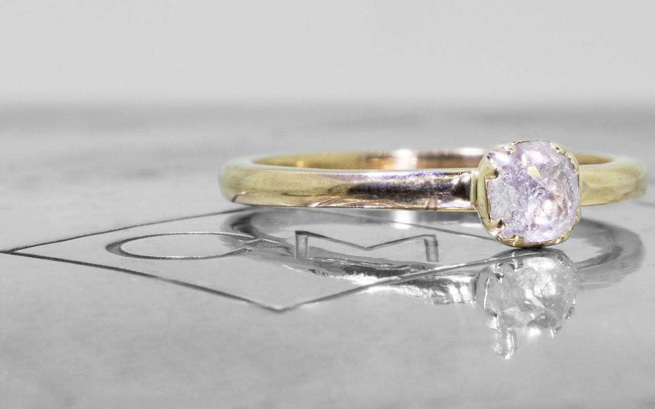 .50 carat  cushion, rose cut icy white bezel set diamond ring set in 14k yellow gold 1/2 round band. 3/4 view on metal background with Chinchar/Maloney logo