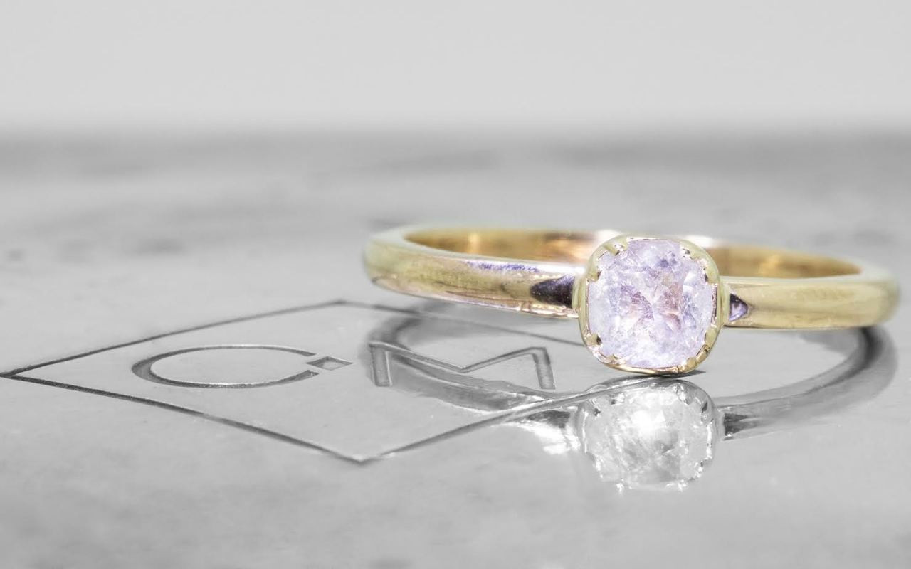.50 carat  cushion, rose cut icy white bezel set diamond ring set in 14k yellow gold 1/2 round band. Front view on metal background with Chinchar/Maloney logo
