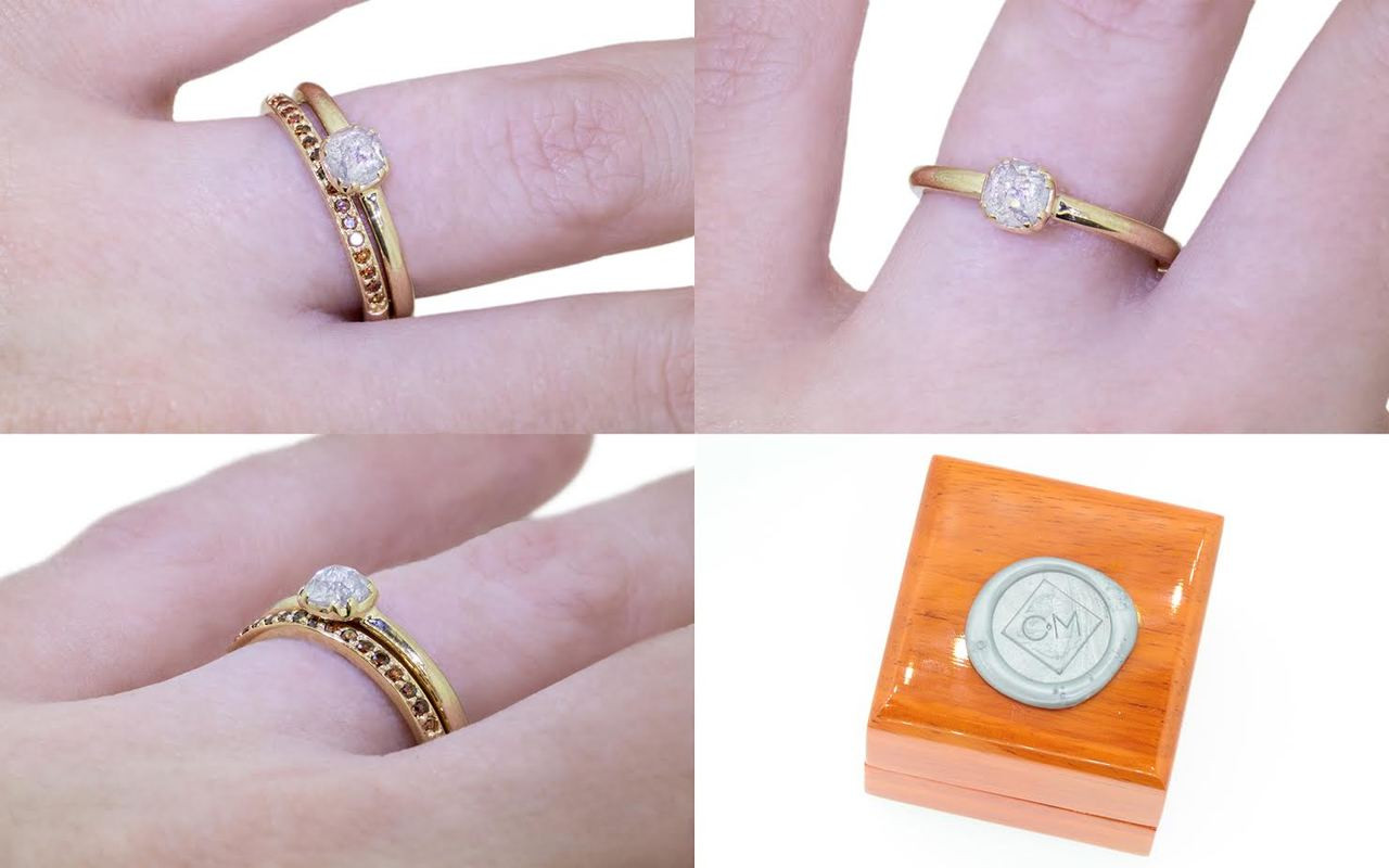 .50 carat  cushion, rose cut icy white bezel set diamond ring set in 14k yellow gold 1/2 round band. With Wedding Band with 16 brilliant cognac diamonds set in 14k yellow gold 1/2 round band on a hand with wooden box stamped with wax seal Chinchar/Maloney logo