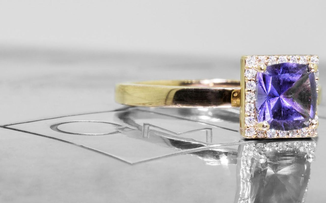 1.38 carat GIA certified square, faceted cut purple sapphire with twenty four brilliant white diamond halo set in 14k yellow gold flat band. 3/4 view on metal background with Chinchar/Maloney logo