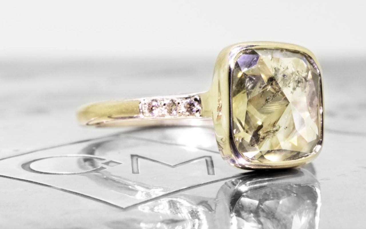 3.20 carat cushion, rose cut translucent rustic champagne bezel set diamond ring set in 14k yellow gold with six 1.2mm brilliant champagne diamonds set in 1/2 round band. 3/4 view on metal background with Chinchar/Maloney logo