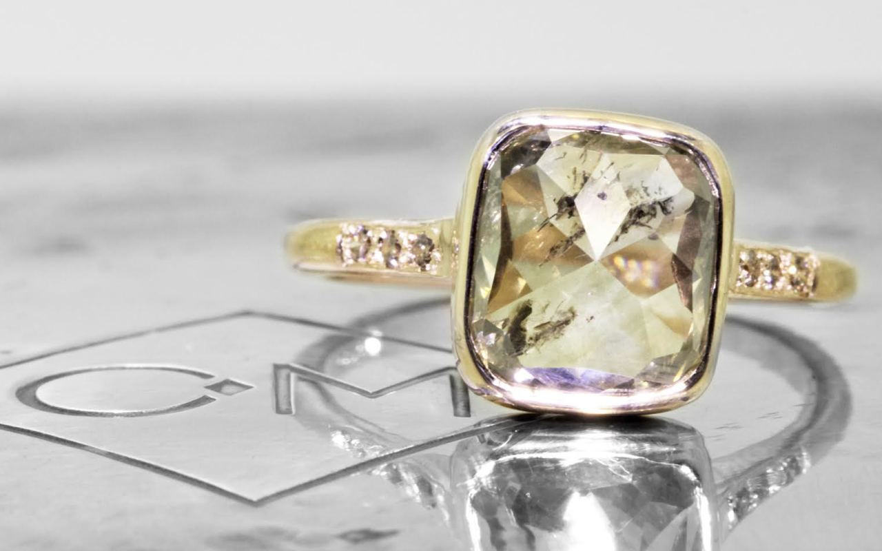 3.20 carat cushion, rose cut translucent rustic champagne bezel set diamond ring set in 14k yellow gold with six 1.2mm brilliant champagne diamonds set in 1/2 round band. Front view on metal background with Chinchar/Maloney logo
